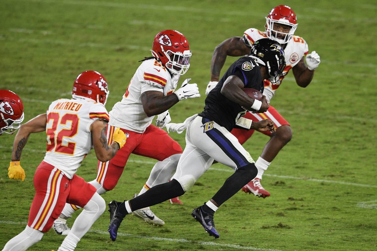 Baltimore Ravens quarterback Lamar Jackson (8) scrambles as he is pursued by Kansas City Chiefs ...