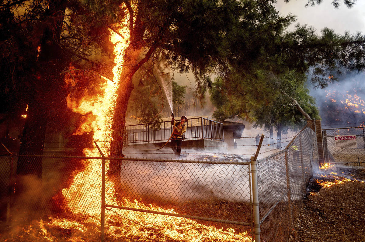 Cal Fire Capt. Jesse Campbell works to save the Louis Stralla Water Treatment Plant as the Glas ...