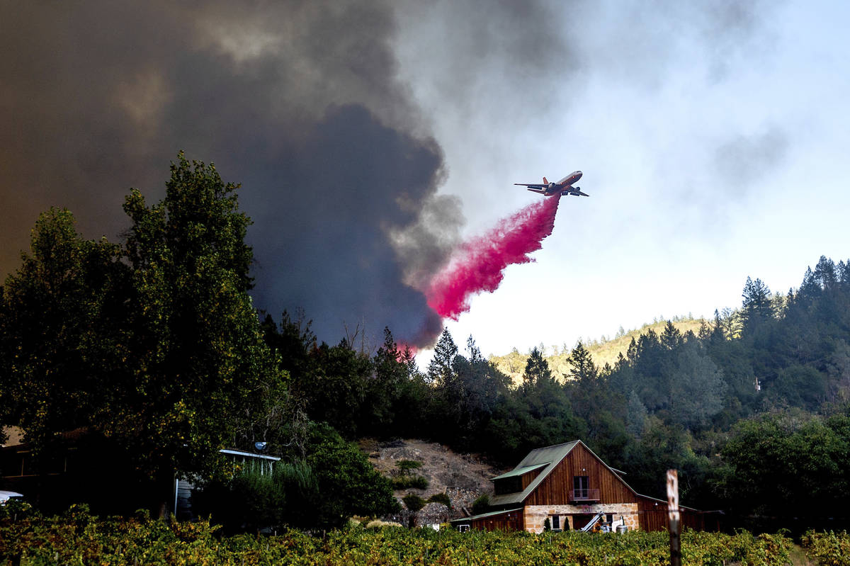 An air tanker drops retardant while battling the Glass Fire in St. Helena, Calif., on Sunday, S ...
