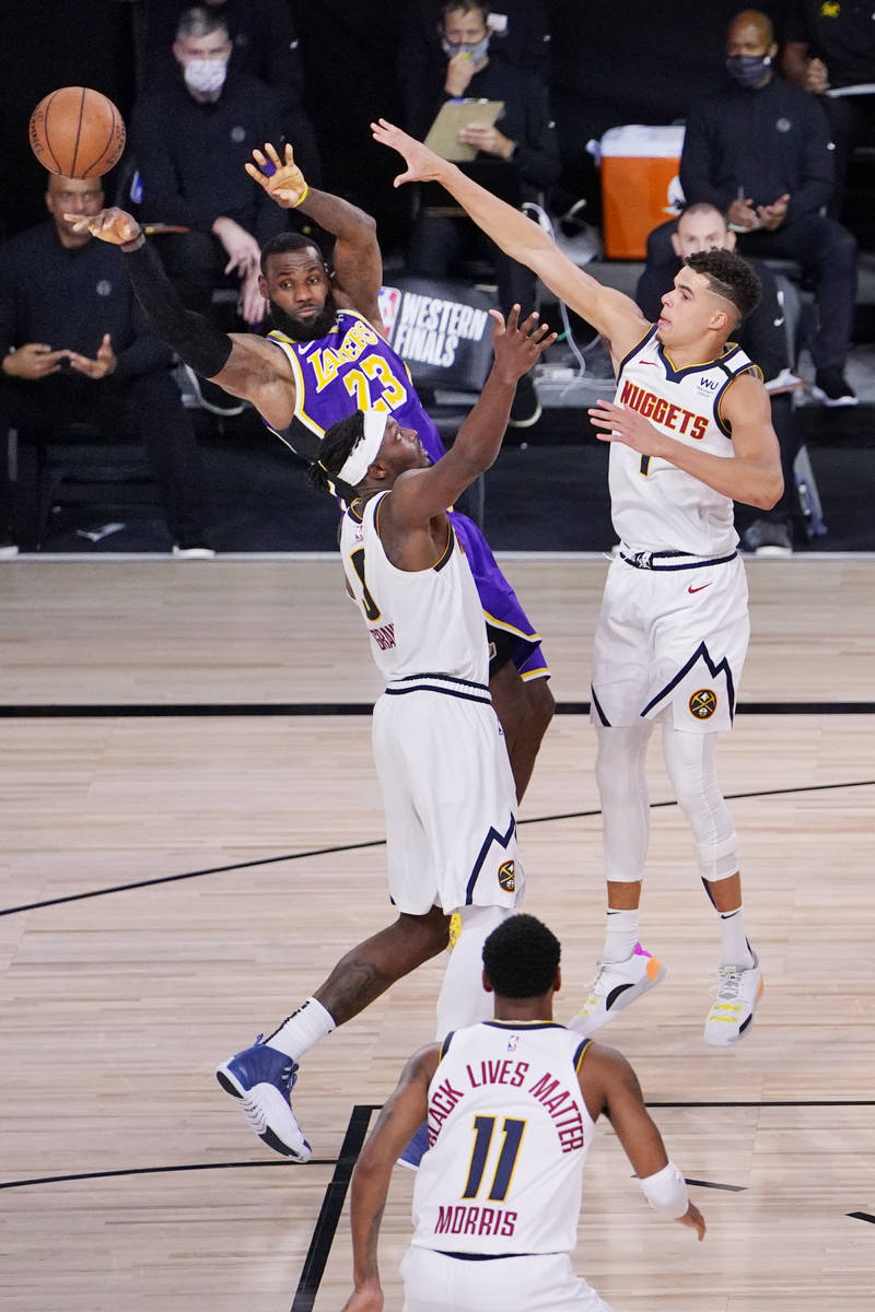 Los Angeles Lakers' LeBron James (23) passes the ball away from Denver Nuggets' Jerami Grant (9 ...