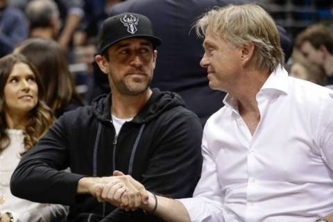 Milwaukee Bucks owner Wes Edens and Green Bay Packers' Aaron Rodgers watch during the first hal ...