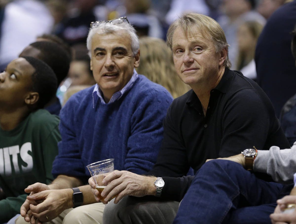 Milwaukee Bucks owners Marc Lasry, left, and Wes Edens, right, watch an NBA basketball game aga ...