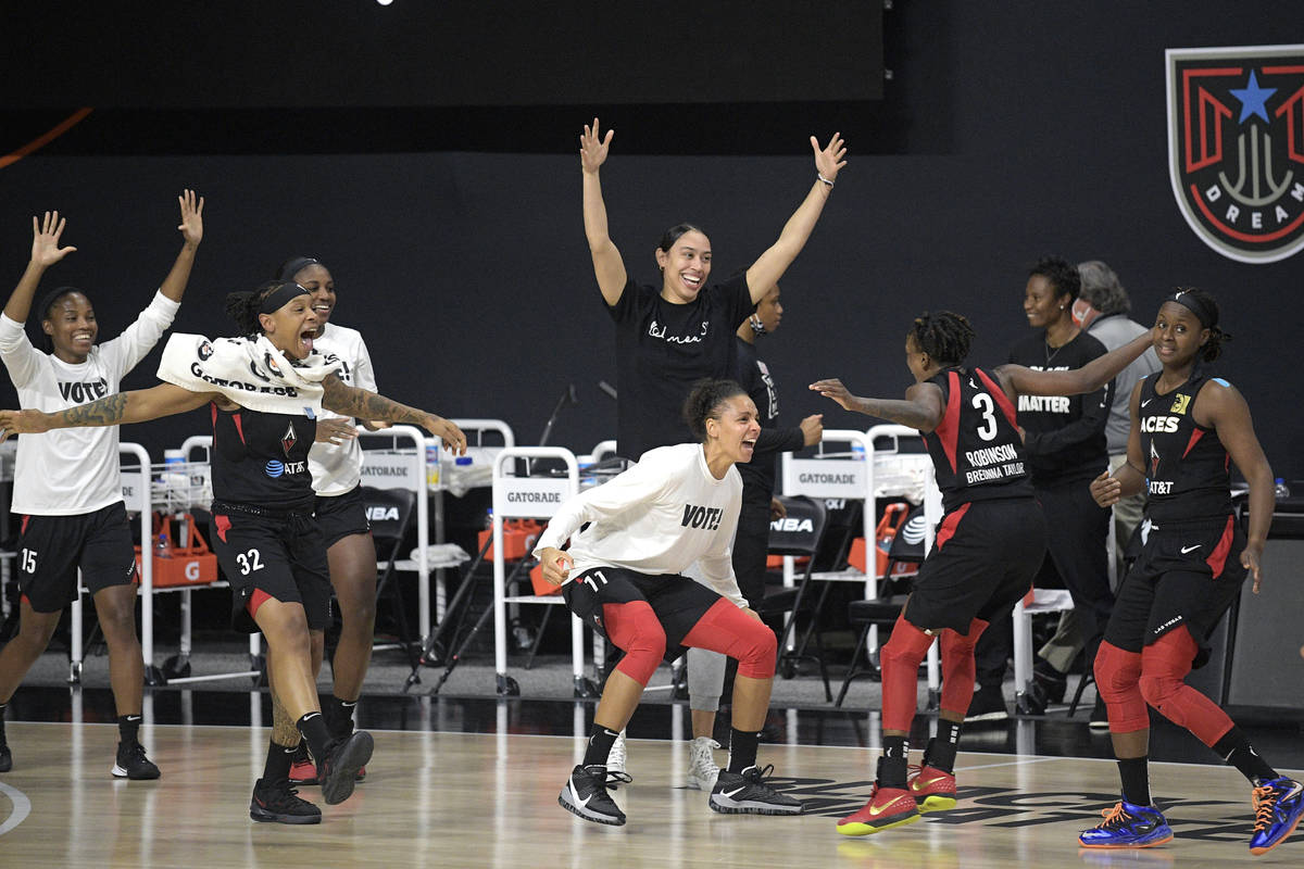 Las Vegas Aces players celebrate after getting the win over the Connecticut Sun in Game 5 of a ...
