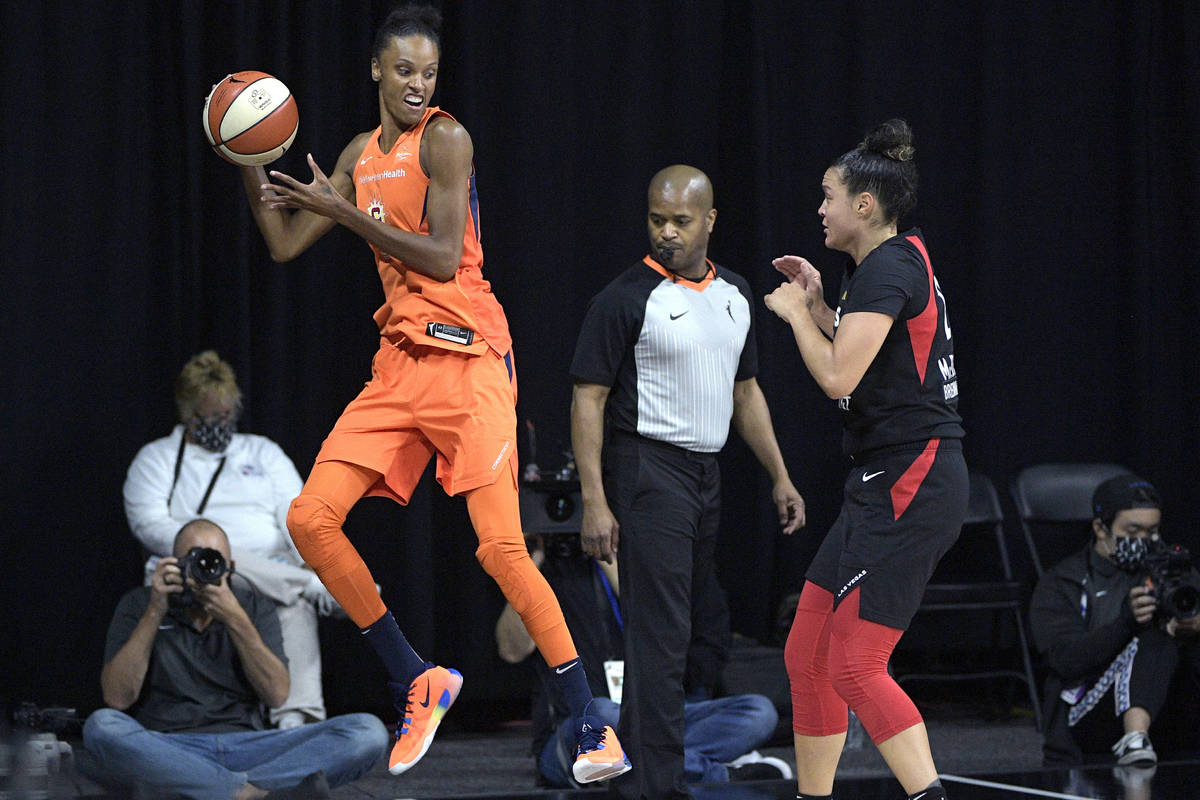 Connecticut Sun forward DeWanna Bonner, left, saves a loose ball from going out of bounds in fr ...