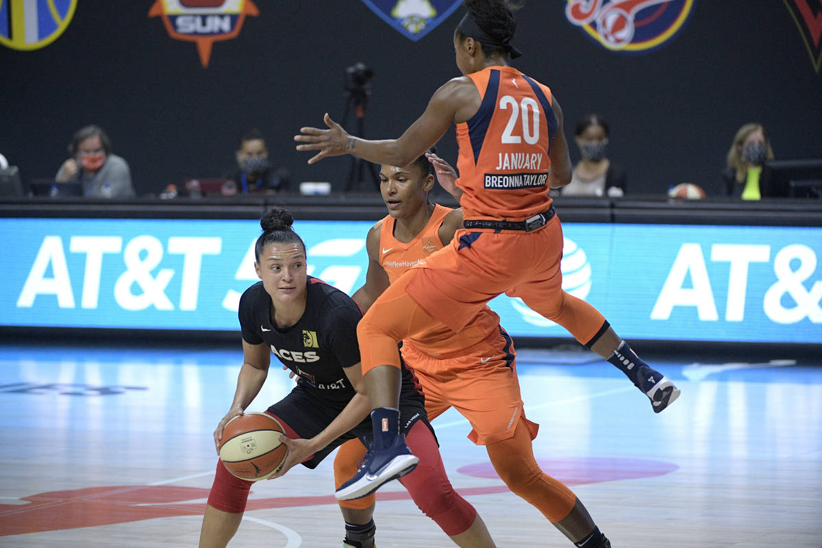 Las Vegas Aces guard Kayla McBride looks to pass the ball while defended by Connecticut Sun for ...