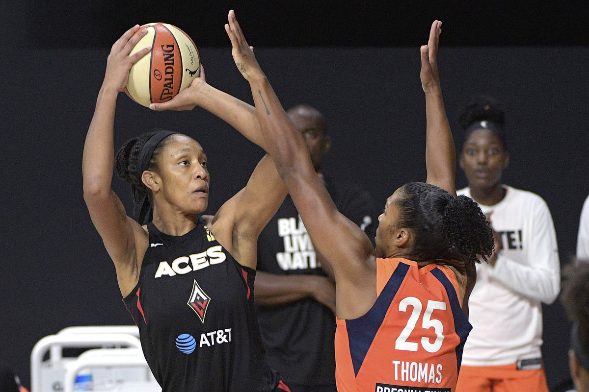 Las Vegas Aces center A'ja Wilson, left, goes up for a shot in front of Connecticut Sun forward ...