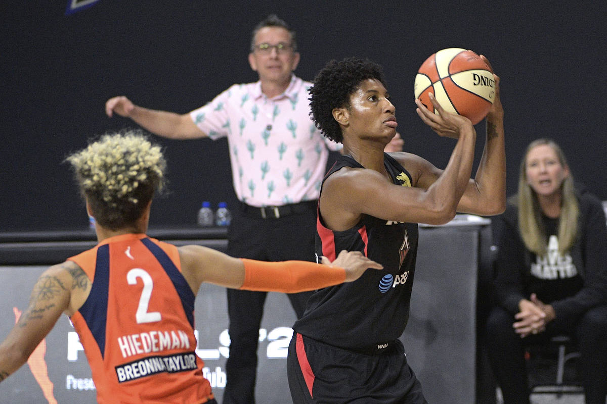 Las Vegas Aces forward Angel McCoughtry, right, sets up for a shot in front of Connecticut Sun ...