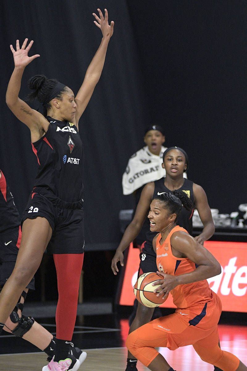Connecticut Sun forward Alyssa Thomas drives to the basket in front of Las Vegas Aces center A' ...