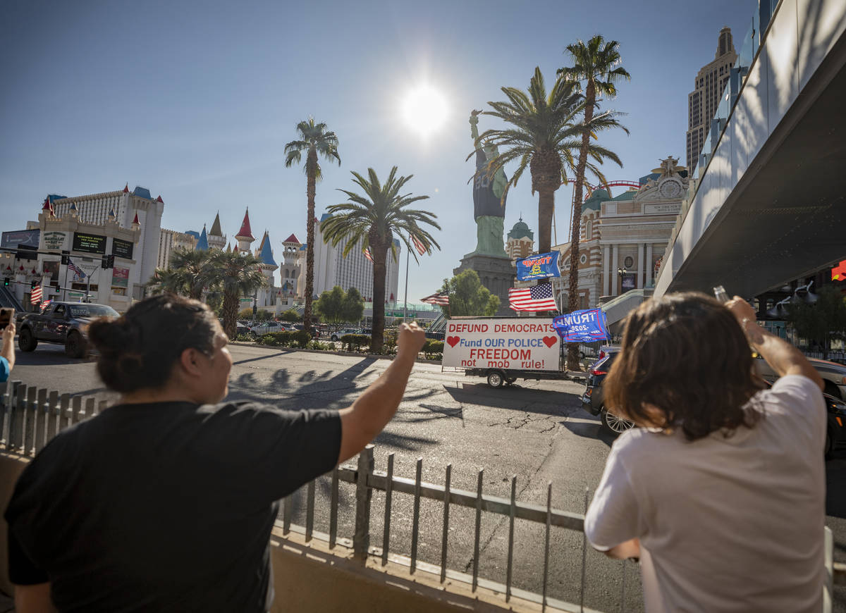 Individuals yell in disagreement as a caravan of Trump supporters ride down the Las Vegas Strip ...