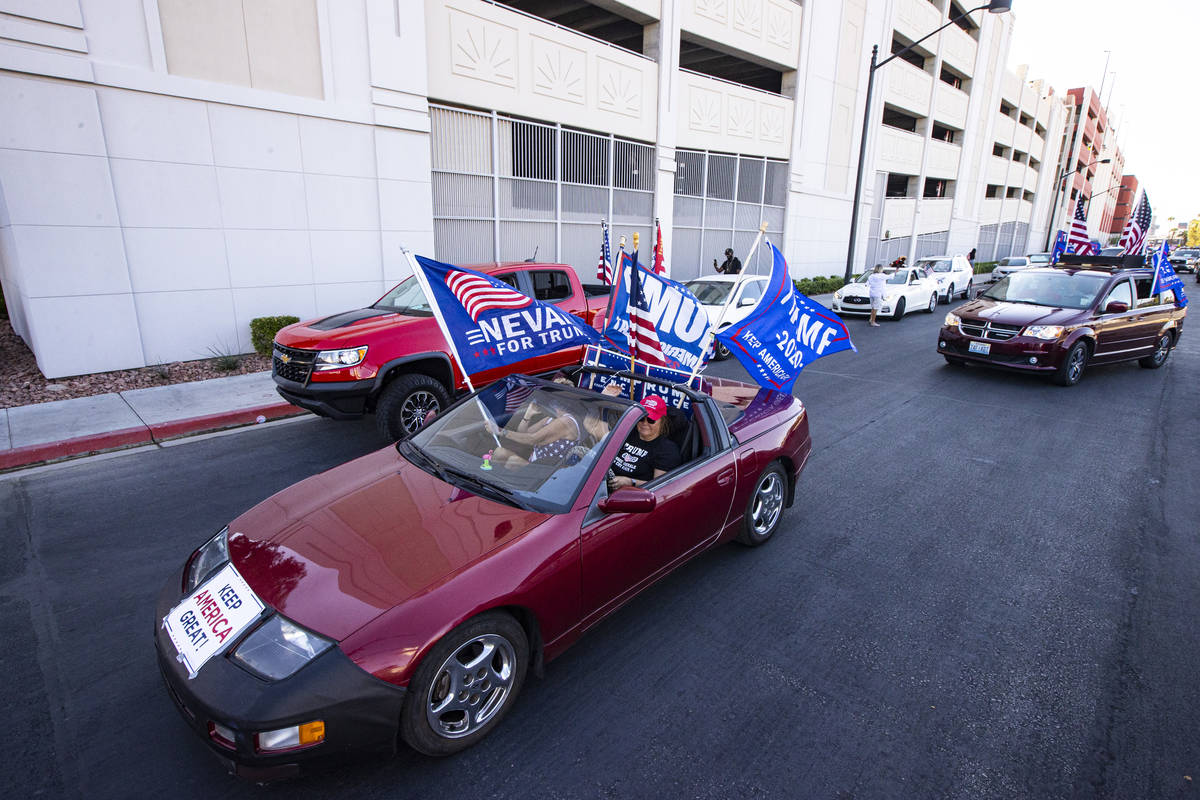 Helen McDonald, of Las Vegas, right, drives her car at the start of a parade in support of law ...