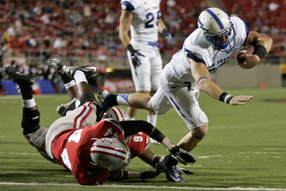 Air Force quarterback Connor Dietz (11) dives past UNLV defenders Kenny Keys (44) and Mark Garr ...