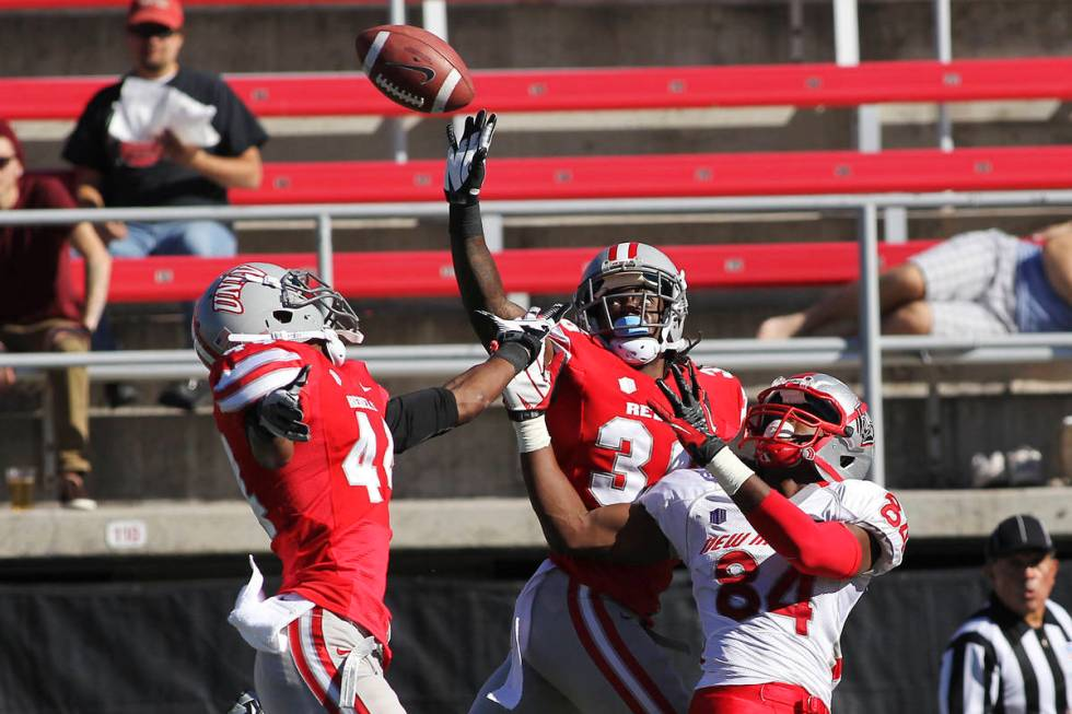 UNLV's Sidney Hodge (36) and Kenny Keys (44) defend a pass intended for New Mexico's Ty Kirk (8 ...