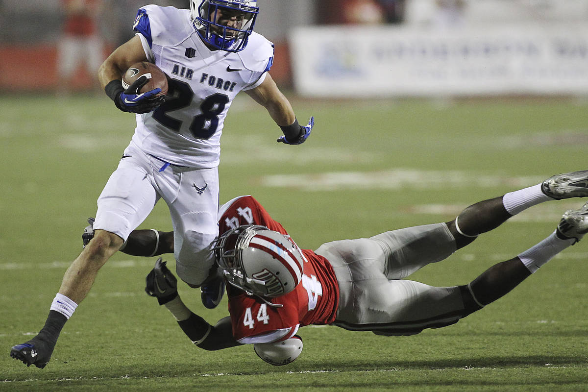 UNLV 's Kenny Keys (44) trips up Air Force Academy's Cody Getz (28) during the first half of fo ...