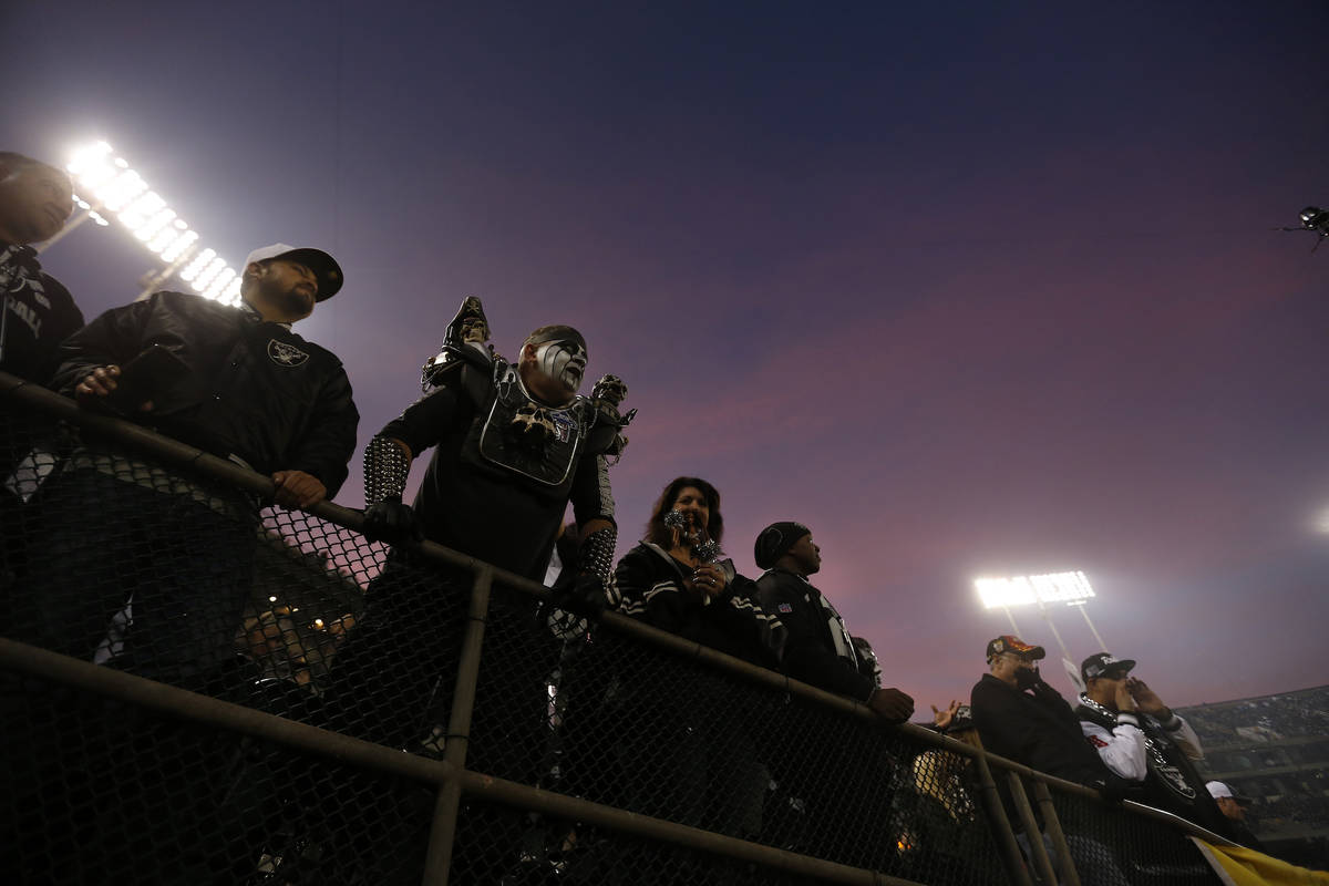 Fans watch as players warm up before an NFL football game between the Oakland Raiders and the L ...