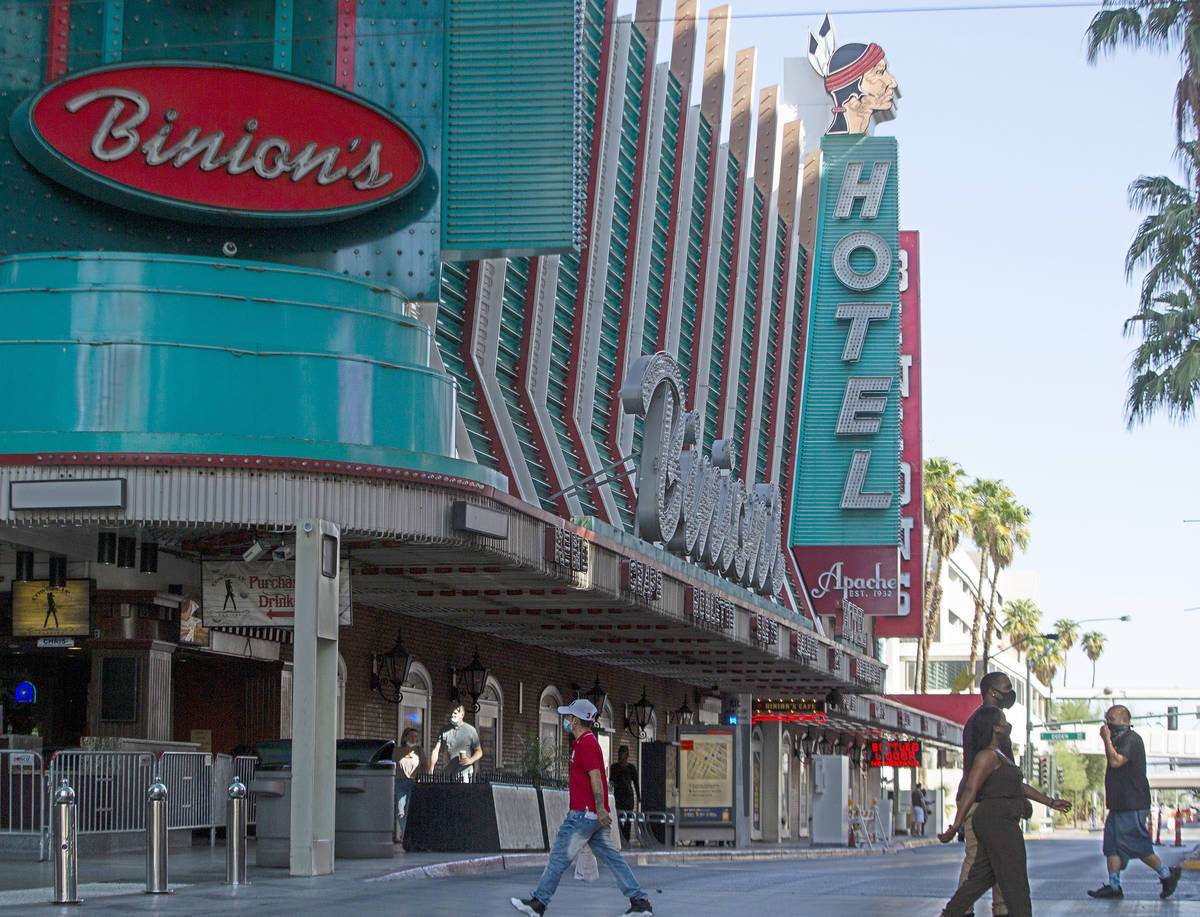 People walk across Fremont Street with Hotel Apache in the background in downtown Las Vegas on ...