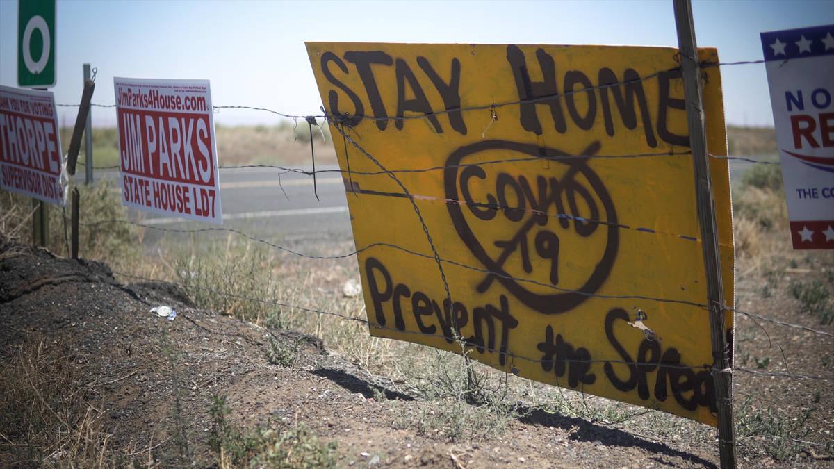 Makeshift, spray-painted signs at the entrance of the Navajo reservation warn visitors and Nava ...