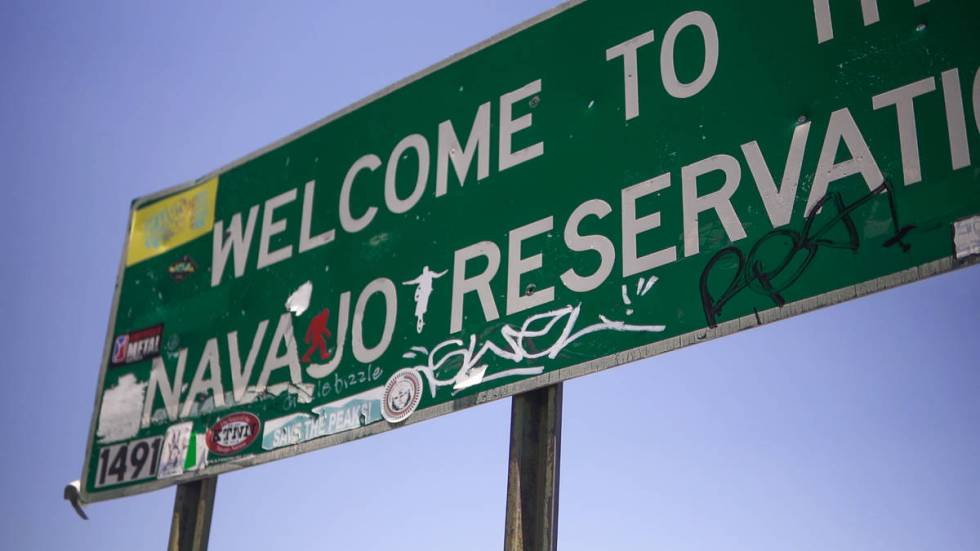 """The Navajo reservation sign is covered in graffiti on July 30, 2020. One sticker reads, """"Save T ..."""