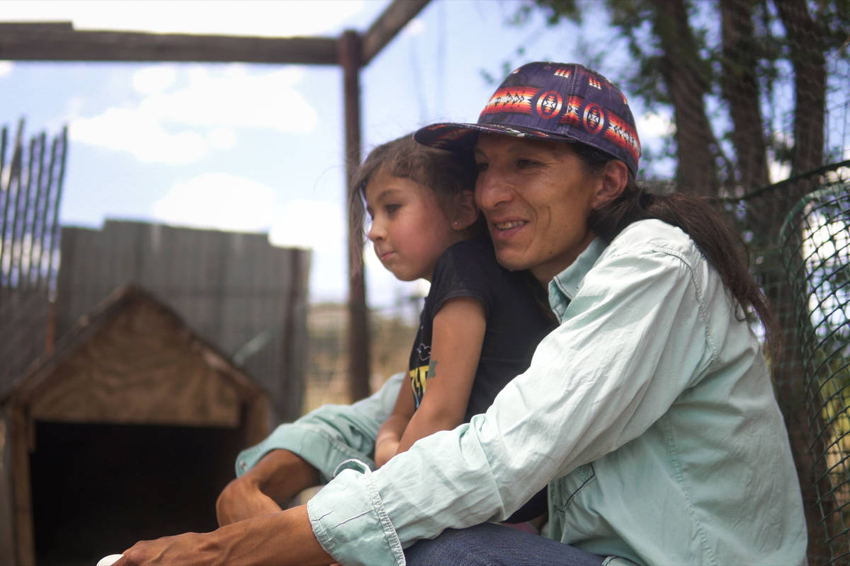 Clayson Benally cuddles with his daughter Zonnie after feeding their chickens on July 29, 2020, ...