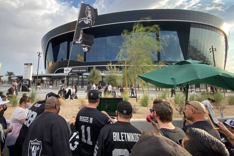 Las Vegas Raiders fans huddled around a 20-inch television on the north end of Allegiant Stadiu ...