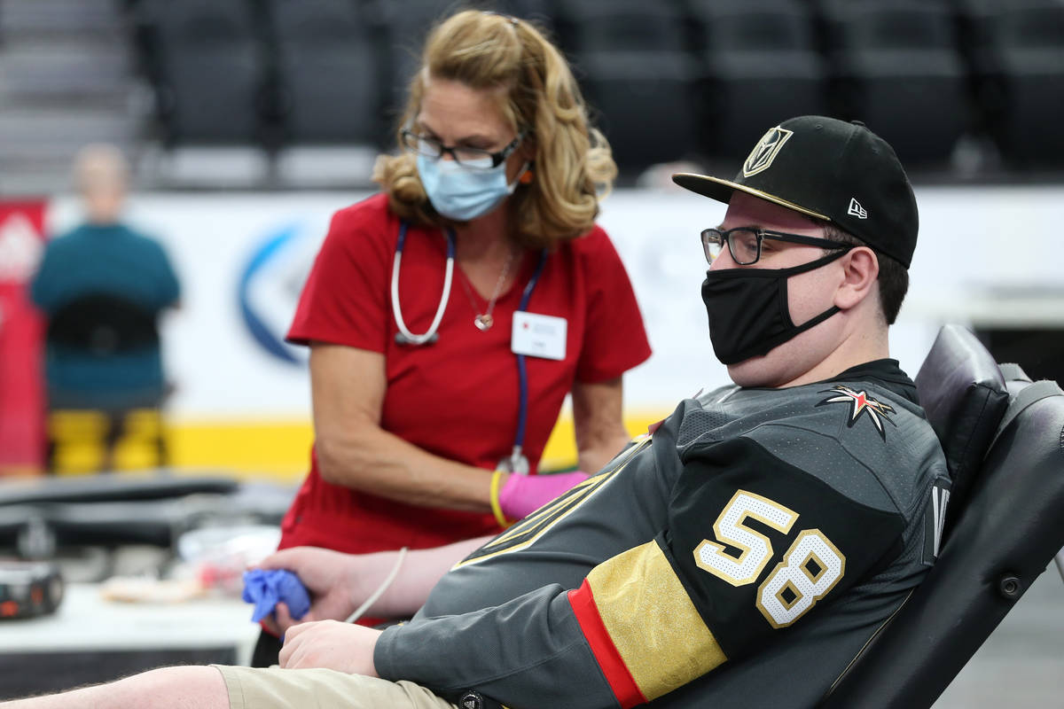 Zach Mueller of Las Vegas, right, gets his blood drawn by American Red Cross team lead Lisa Bra ...