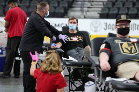 Dave Goucher, a Vegas Golden Nights television voice, center, participates during a blood donat ...