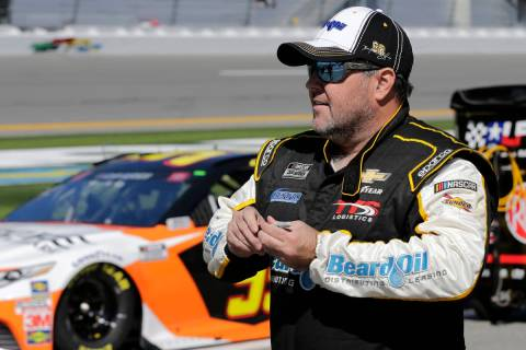 Brendan Gaughan walks along pit road during NASCAR auto race qualifying at Daytona Internationa ...