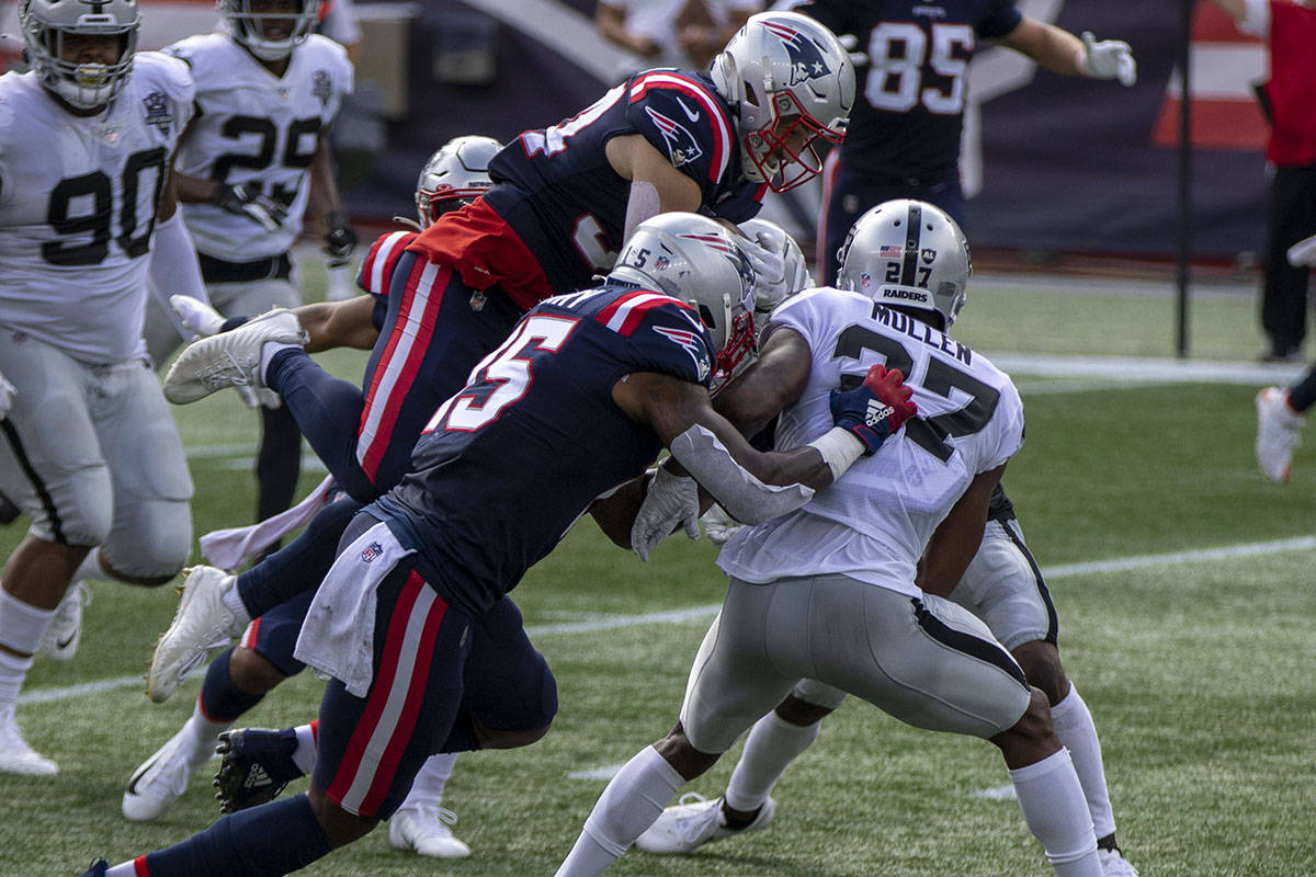 New England Patriots running back Rex Burkhead (34) leaps over Las Vegas Raiders cornerback Tra ...