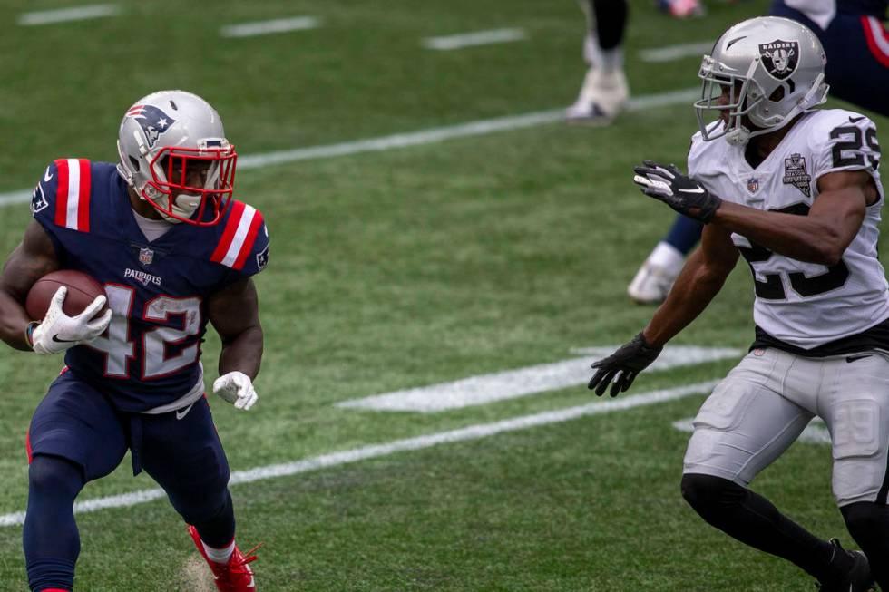New England Patriots running back J.J. Taylor (42) looks to run past Las Vegas Raiders free saf ...