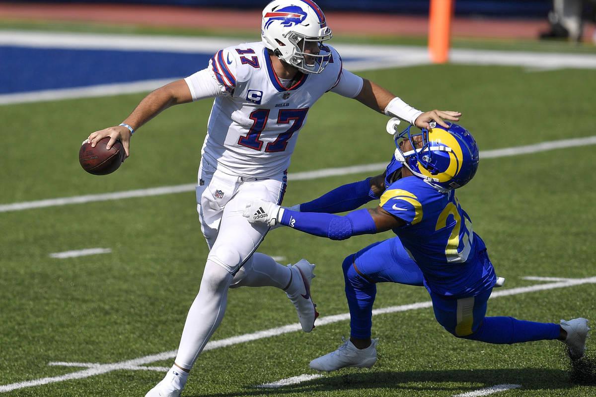Buffalo Bills quarterback Josh Allen, left, stiff arms Los Angeles Rams cornerback Troy Hill, r ...