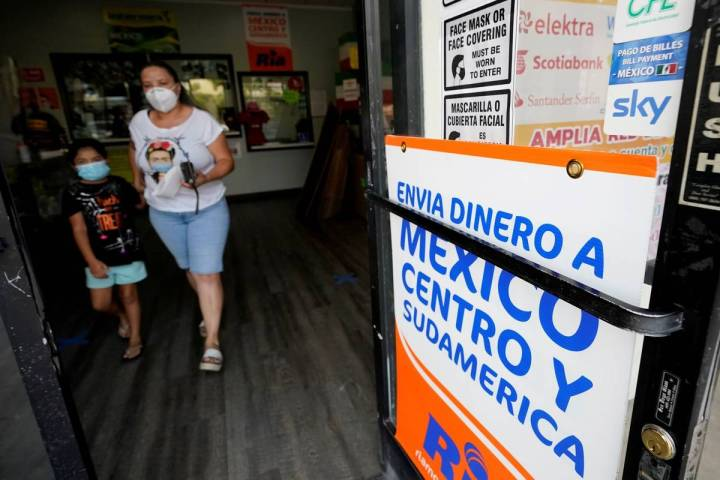 A woman leaves a store offering services to send remittances to Mexico and Central America, Fri ...