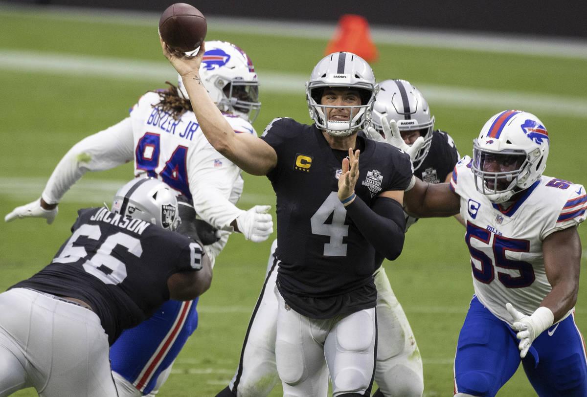 Las Vegas Raiders quarterback Derek Carr (4) just gets the ball away past Buffalo Bills defensi ...