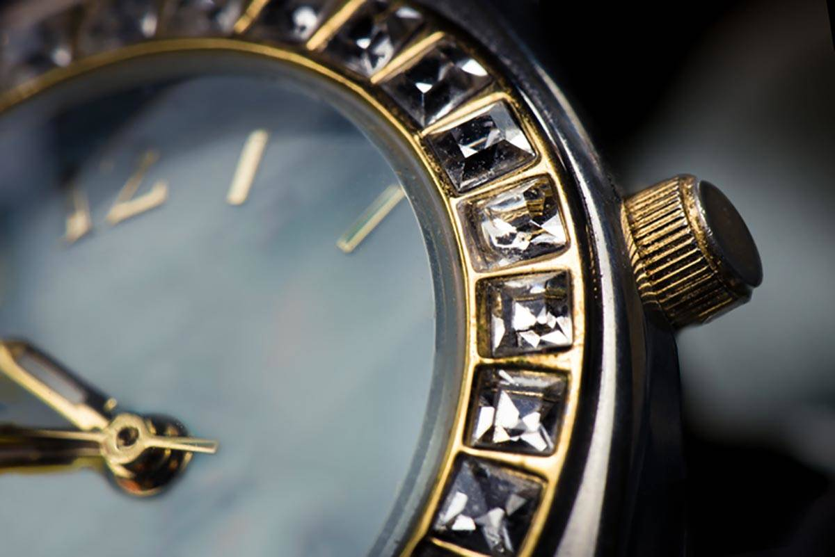 Macro close up of watch face with square diamonds around face.