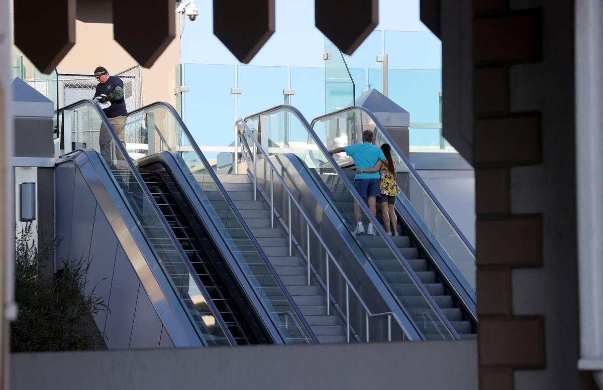 A worker performs scheduled maintenance on an escalator for the pedestrian bridge between Excal ...