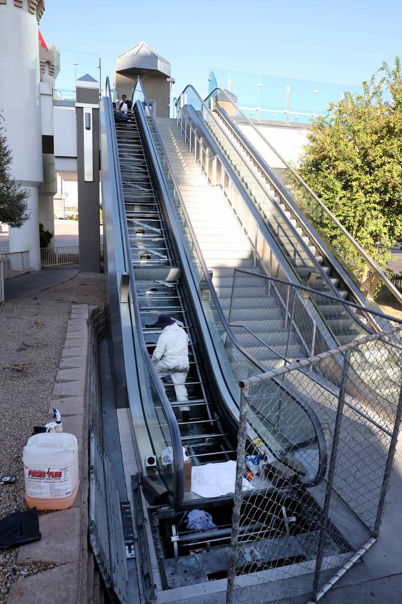 Workers perform scheduled maintenance on an escalator for the pedestrian bridge between Excalib ...