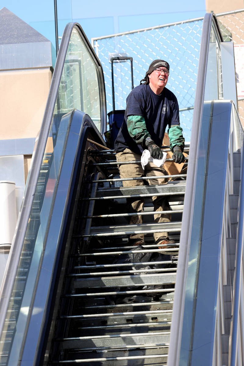 A worker who declined to give his name performs scheduled maintenance on an escalator for the p ...