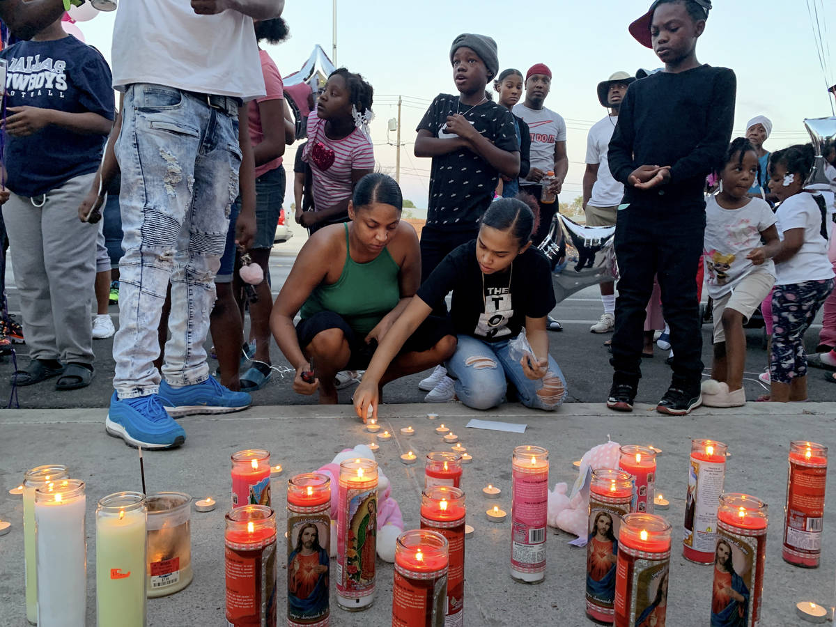 Aunts of 1-year, 9-month-old Sayah Deal, Katie Porter, left, and Christina Scott, light candles ...