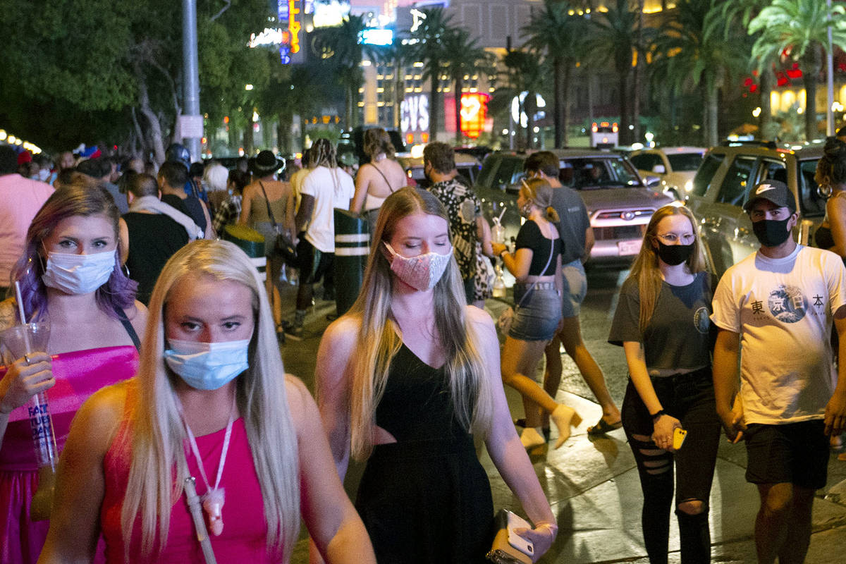 A crowd crosses Bellagio Drive during Labor Day weekend on Saturday, Sept. 5, 2020, on the Las ...