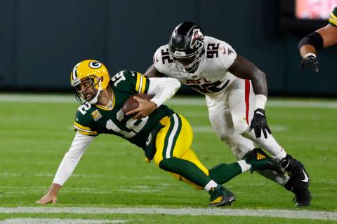 Green Bay Packers quarterback Aaron Rodgers (12) is tackled by Atlanta Falcons' Charles Harris ...