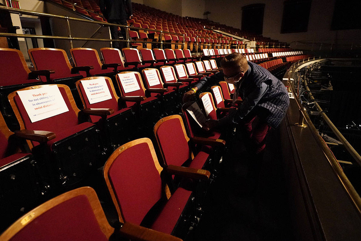 A member of the production staff puts labels on seats in an effort to keep seats socially dista ...