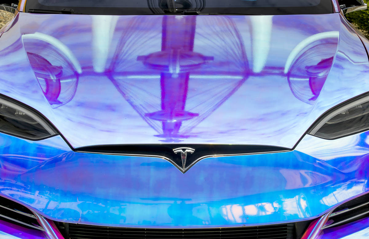 The High Roller is reflected on the hood of a Tesla parked in the Tesla Supercharger station ne ...