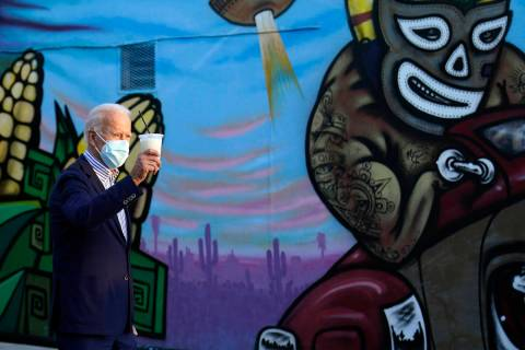 Democratic presidential candidate former Vice President Joe Biden holds up a drink he received ...