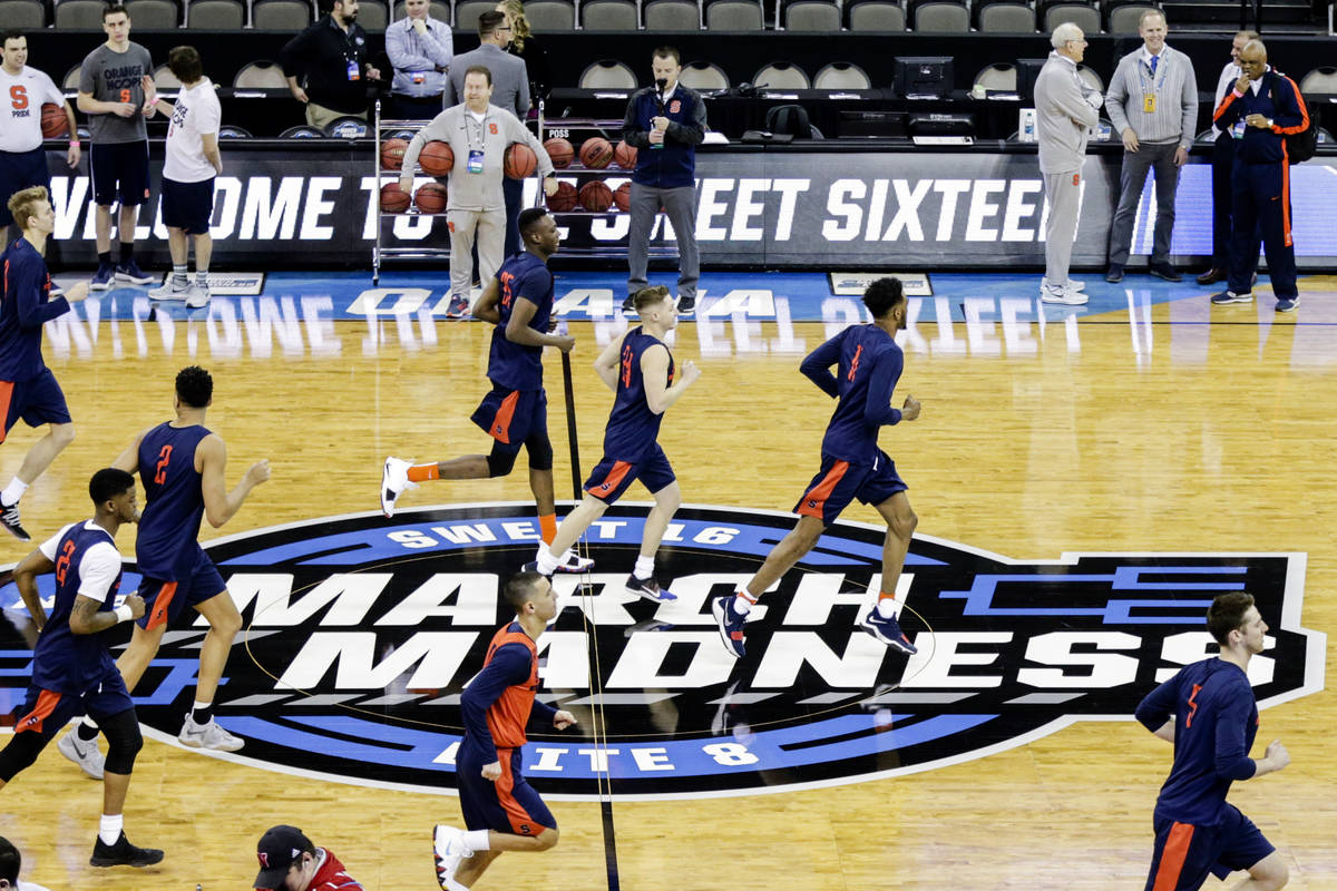 Syracuse players warm up during practice at the NCAA men's college basketball tournament, in Om ...