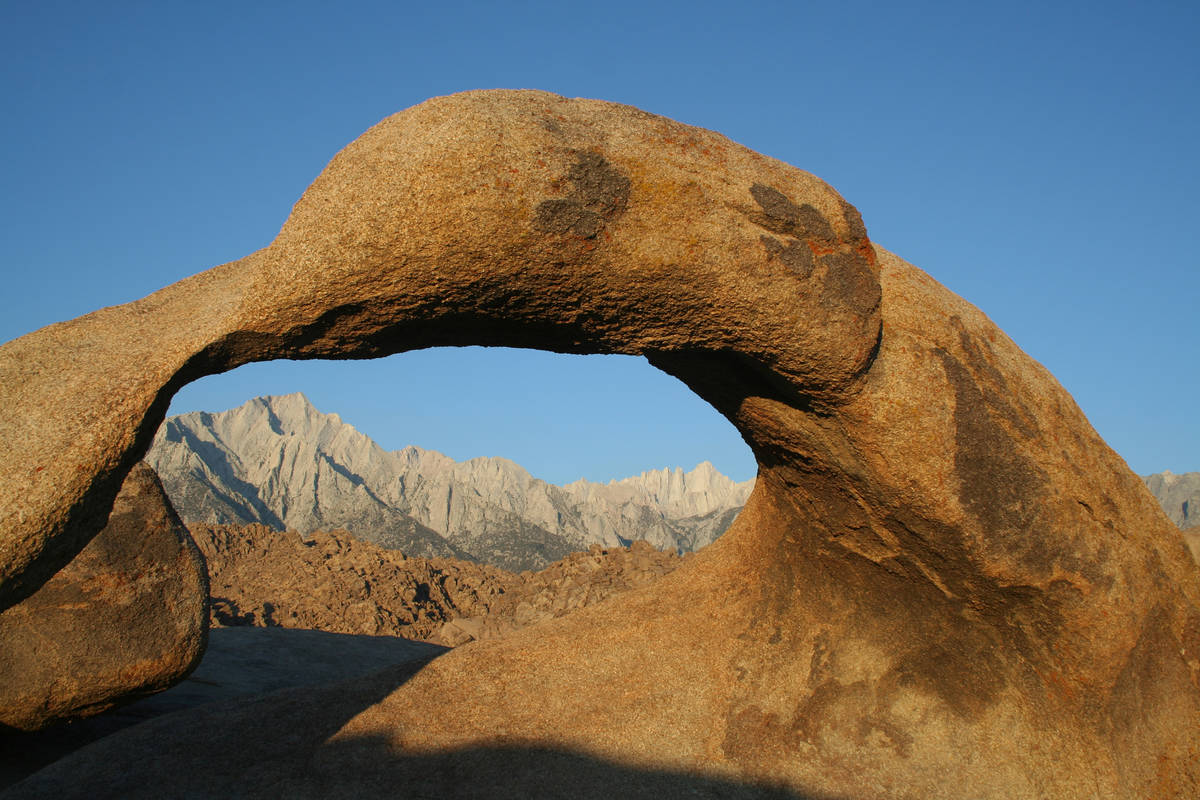 Mobius Arch frames Lone Pine Peak, left, at 12,949 feet, and Mount Whitney at 14,505 feet. (Deb ...