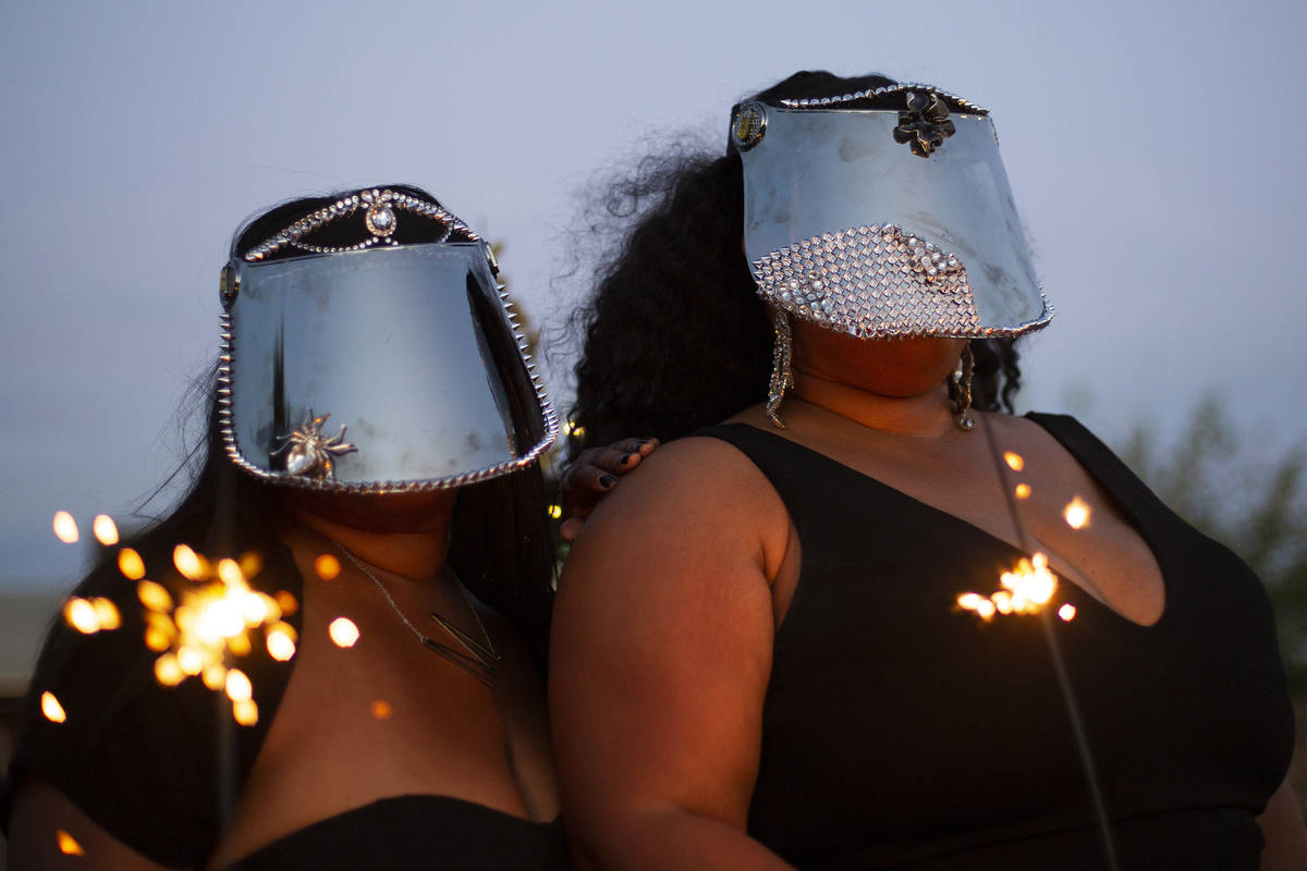Kwazi Yimam and Monet Owens pose with their custom face shields at a Noir Culinary Experience e ...