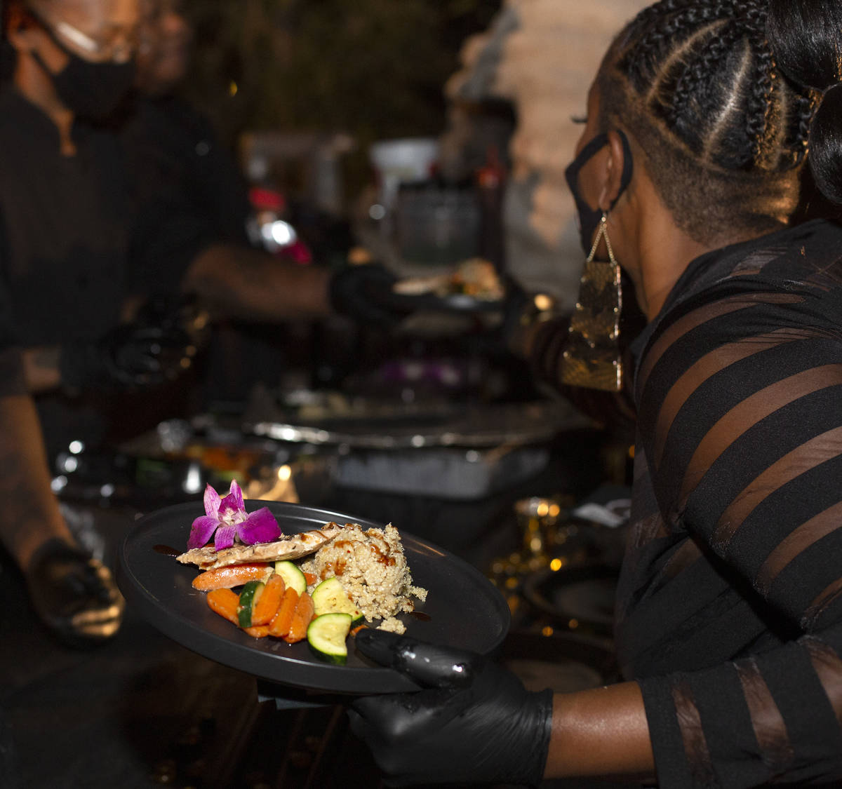Emika Porter picks up plates to serve at a Noir Culinary Experience dinner to promote Black che ...
