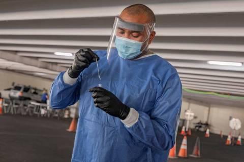 Nevada National Guard Sgt. combat medic Steve Sanson demonstrates a walk-up COVID-19 test at th ...