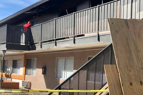 A maintenance worker at Corona Del Sol Apartments cleans up debris after a fatal fire in the ea ...
