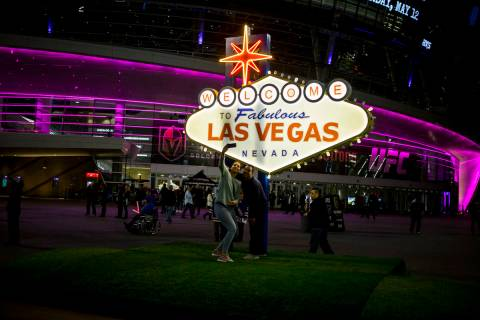 Pep rally attendees take photos with a scale model of the Las Vegas sign on Toshiba Plaza outsi ...