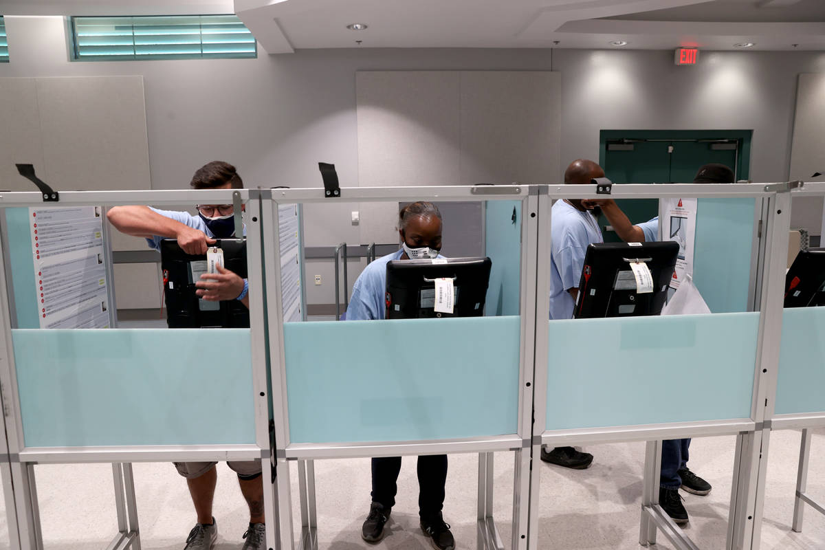 Clark County election workers Nestor Ruizvelasco, left, Tameka Balaka set up voting booths at t ...