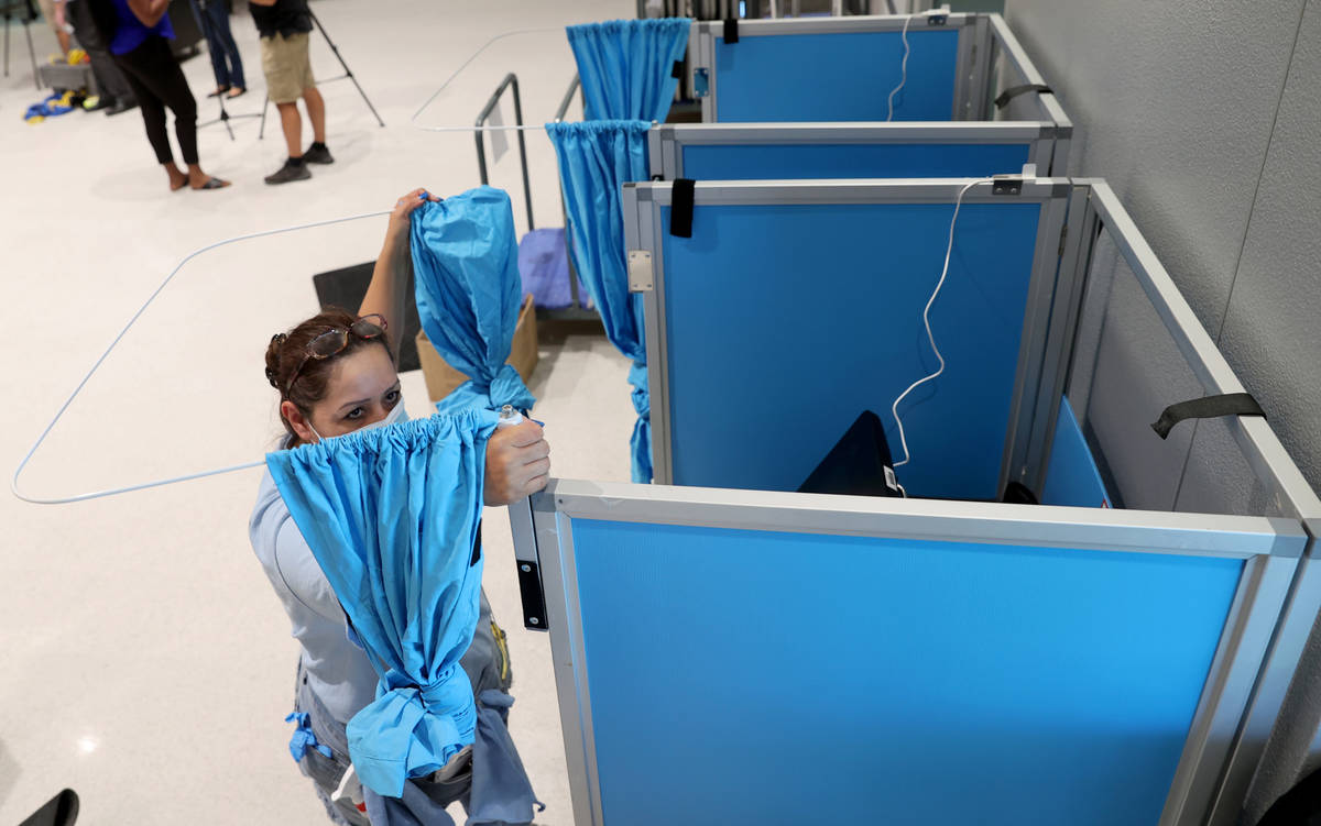 Elections workers, including election assistant Sol Cardenas, set up voting booths at the Cora ...